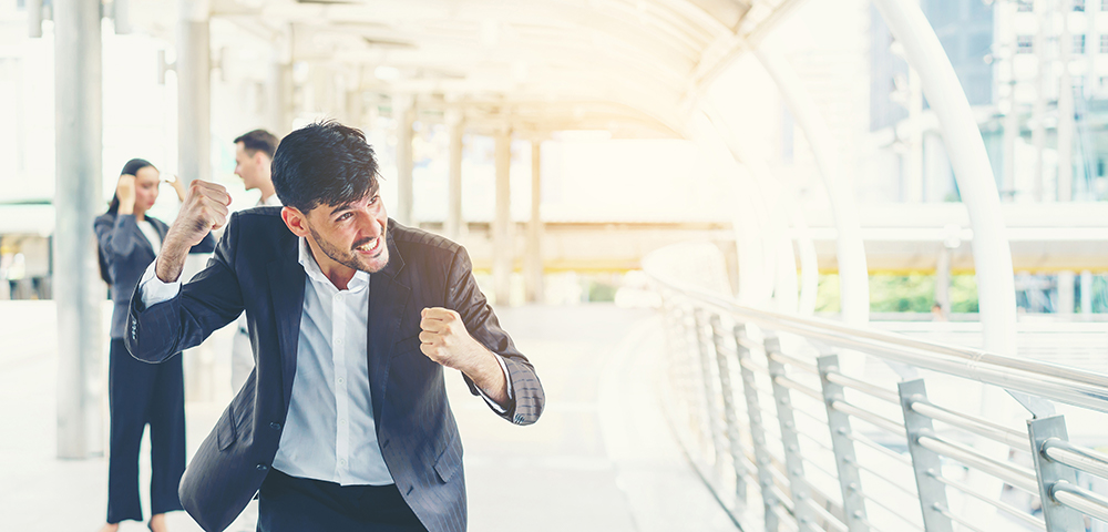 Negotiating salary and benefits - Man in suit with winning stance