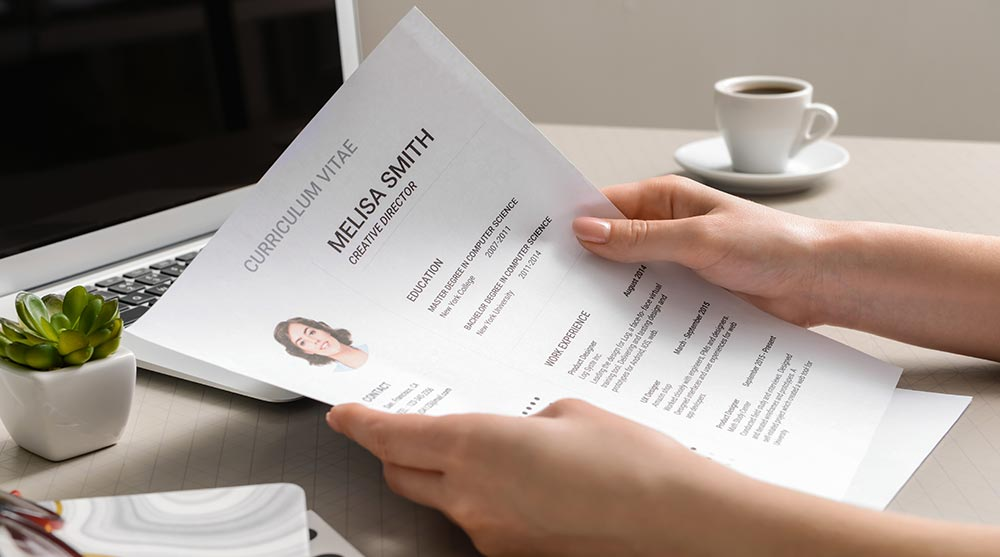 What is a Recruiter and How Do I Find One? Recruiter looking at resume