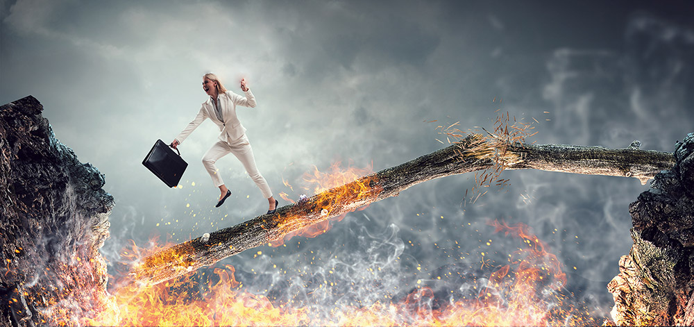 How to Reject a Job Offer Without Burning Bridges - woman crossing burning bridge